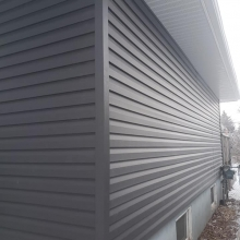 "Full exterior renovation. Royal Estate Ironstone siding, 1"" enerfoil insulation, Clipstone accent around door (Black Rundle color), Custom aluminum window capping and Pressure treated deck."