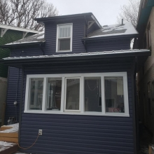 New Royal estate siding in Marine Blue color with accented ironstone corners. Front gable done in Portmouth Shake Gray Moss color. All Weather patio door installed in place of a 32 exterior door. All soffit, fascia and eaves done in black to tie it all